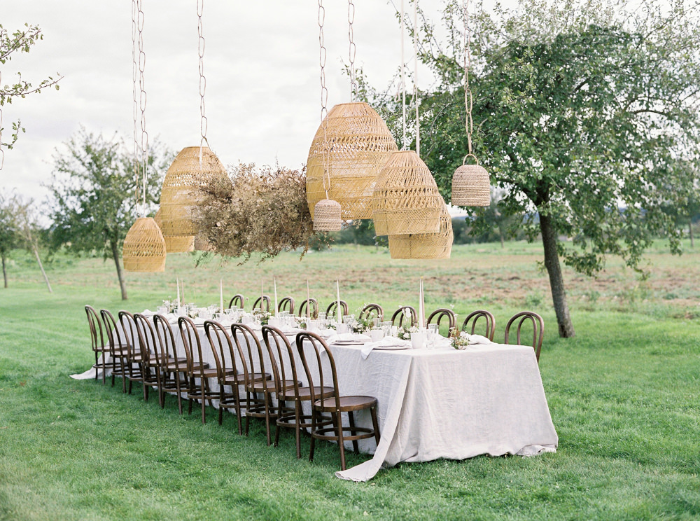 Alfresco dining table with hanging floral cloud and rattan chandeliers by Lucy Davenport Photography.