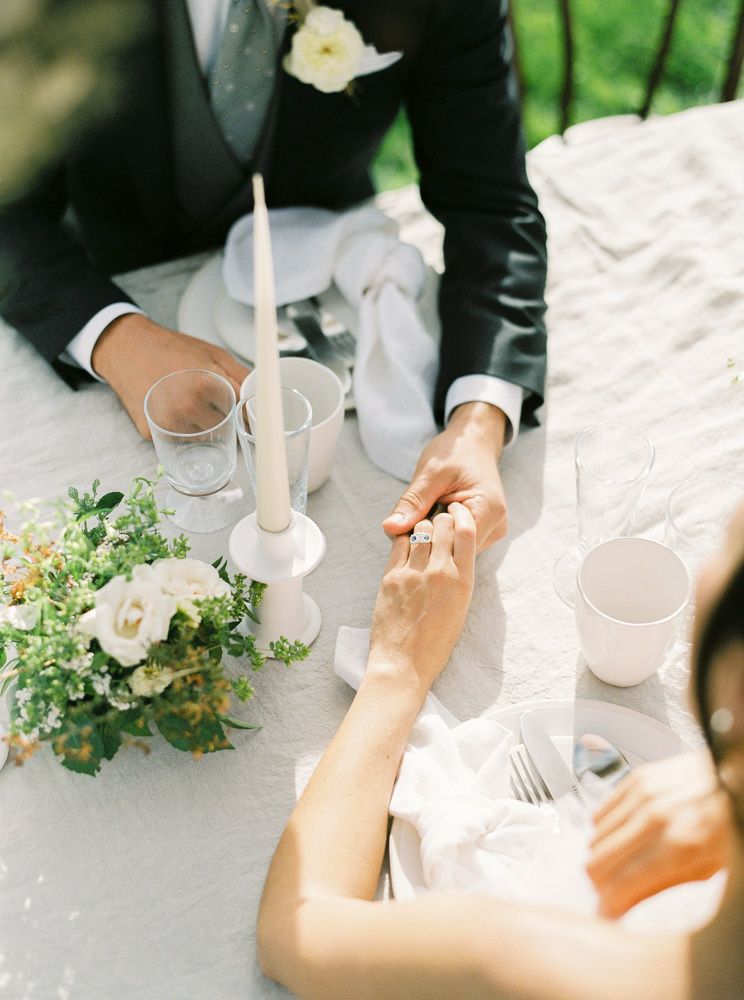 Bride and groom holding hands across the table.