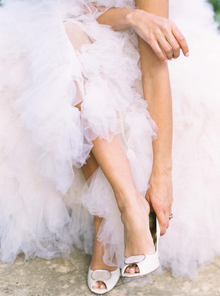 Bride putting on Freya Rose pearl wedding shoes.