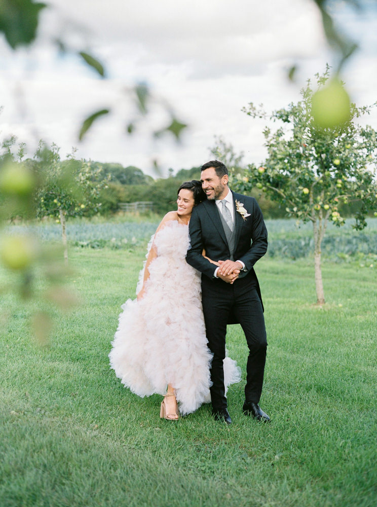 Bride and groom walking though the apple trees at Daylesford Organic.