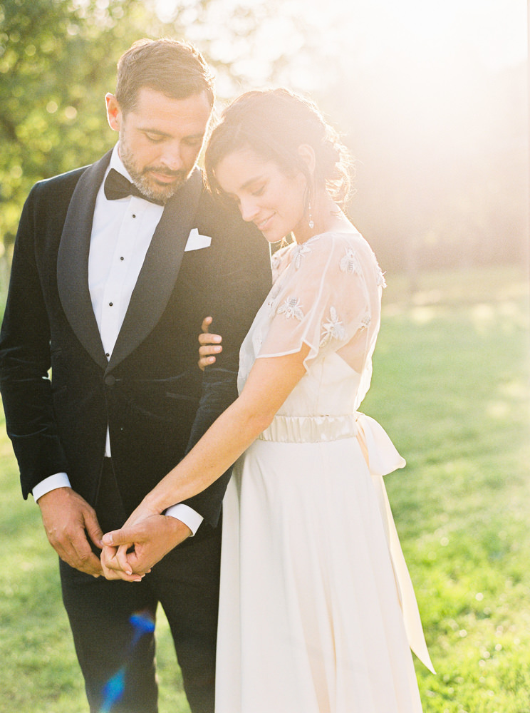 Bride wearing Halfpenny London, hugging groom in the sunset at Daylesford.